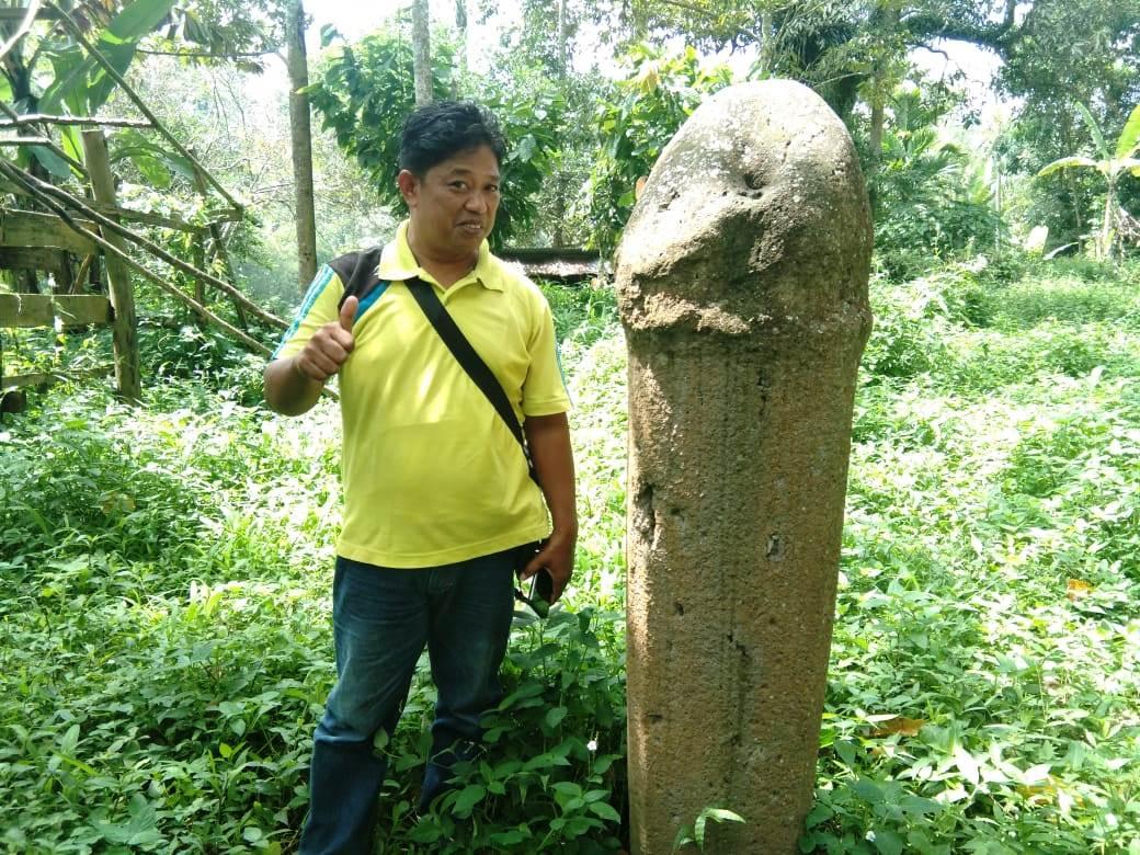 Salah satu warga Tanah Datar berfoto di samping batu prasasti berbentuk alat kelamin yang ditemukan di Nagari Tanjung Tanah Datar Sumbar (M Rafi / Mattanews.co)
