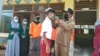 Wali Nagari Batu Taba Desriyanto memasangkan masker ke salah satu pelajar SDN 10 Batu Taba Tanah Datar Sumbar (M Rafi / Mattanews.co)