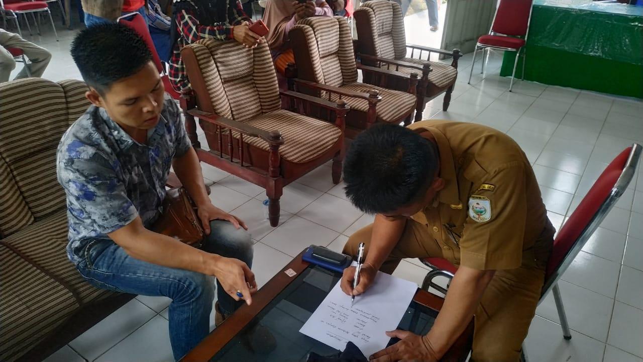 Sekcam Baturaja Barat menandatangani surat bermaterai, yang berisi akan segera mengurus pencairan gaji para pejabat RT dan RW yang belum cair (Satrio / Mattanews.co)